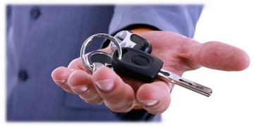 Open hand of a man offering keys to rental car.